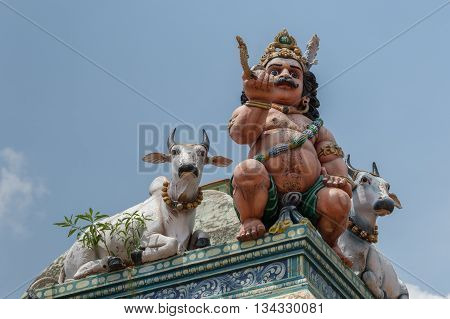 Chettinad India - October 17 2013:Detail of the Shiva temple at Kottaiyur shows half-naked Ayyanar on wall in company of two bulls against blue sky.