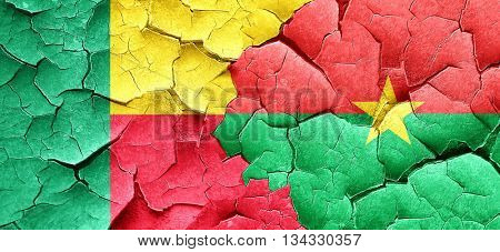 Benin flag with Burkina Faso flag on a grunge cracked wall