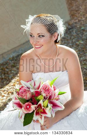 A newly married bride squats down to take a short break from painful shoes. She has a smile on her face and a beautiful bouquet.