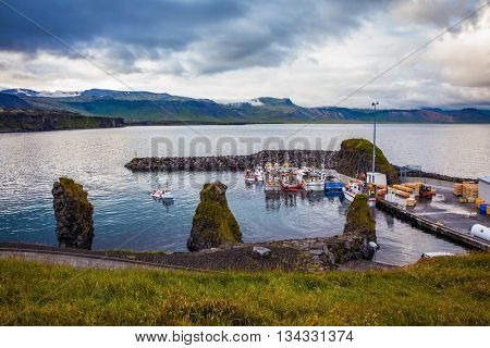 Sunset on the fjord in Iceland. White and red fishing boat in the harbor pier village Arnastapi
