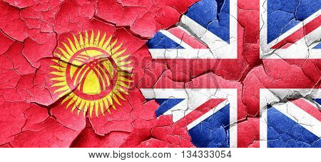 Kyrgyzstan flag with Great Britain flag on a grunge cracked wall