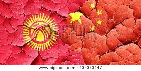 Kyrgyzstan flag with China flag on a grunge cracked wall