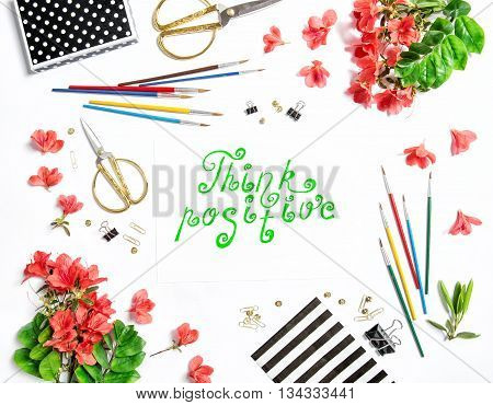 Flat lay with sketchbook flowers office supplies on white background. Quote Think positive