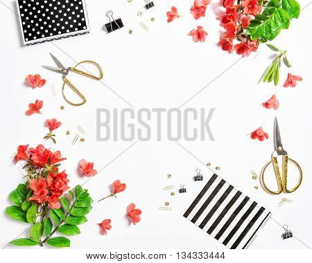 Artistic flat lay with sketchbook flowers office supplies on white background