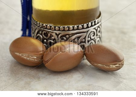 Bottle with moroccan argan oil and nuts close up