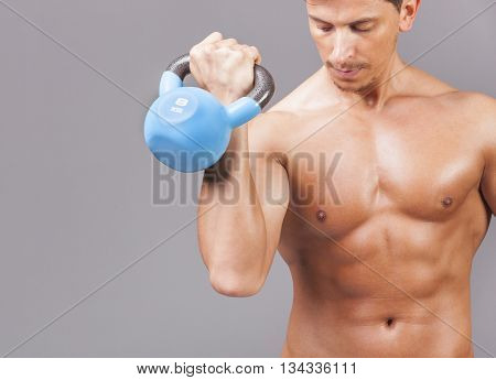 Fit young man exercising with kettle bell on grey background