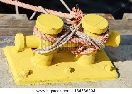 Yellow mooring bollard with blue rope in marina close up