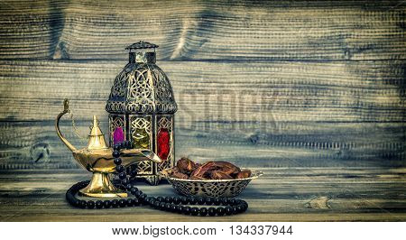 Antique arabic lantern and islamic rosary beads. Oriental holidays decoration with dates fruits. Vintage style toned picture