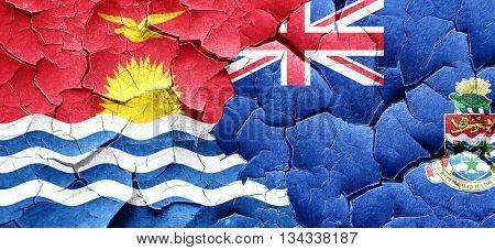 Kiribati flag with Cayman islands flag on a grunge cracked wall