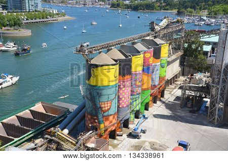 VANCOUVER BC CANADA JUNE 10 2015: Ocean Concrete is Granville Island last tie to to its industrial past, and now 6 concrete silos are being transformed by two famous Brazilian street artists Os Gemeos
