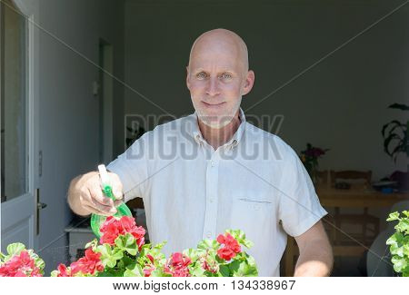 mature man watering the flowers near the windows