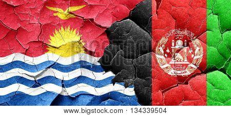 Kiribati flag with afghanistan flag on a grunge cracked wall
