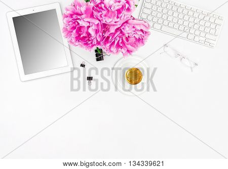 Feminine office workplace with coffee and flowers. Mockup with digital tablet screen