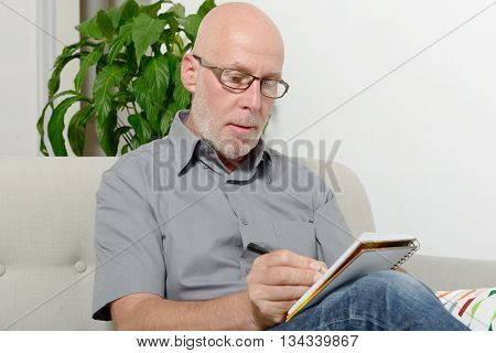 mature man sitting in a sofa taking notes