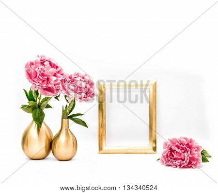 Golden picture frame and pink flowers. Minimal style decoration with space for your image text work