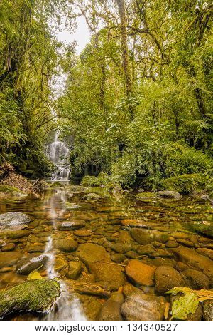 River and Waterfall flowing through green mold rocks at Cerro Dantas national reserve in Costa Rica