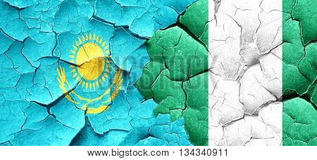 Kazakhstan flag with Nigeria flag on a grunge cracked wall
