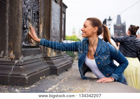 a young woman on Charles Bridge in Prague touching the shiny plaque and making a wish.
