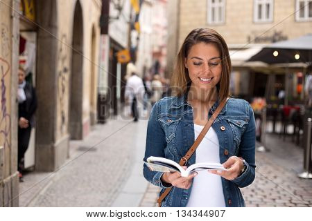 young tourist reading her guide book in the street