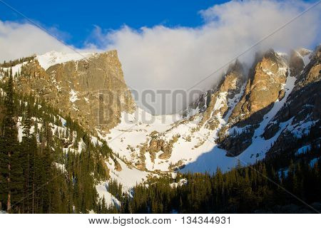 Clouds swirl over Hallett and Flattop peaks in Rocky Mountain National Park in Estes Park Colorado