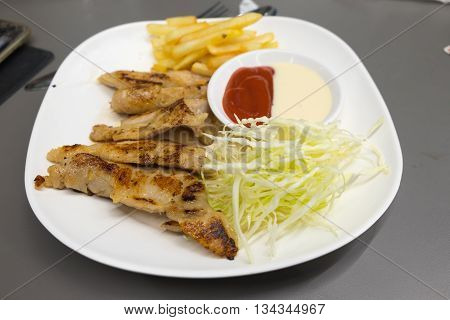 pork steak with french fries and salad.