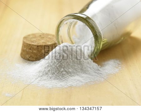 bottle of baking soda on the wooden table