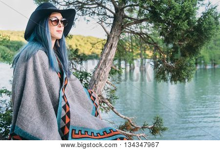 Beautiful fashionable young woman wearing in hat and poncho resting on coast of lake in summer