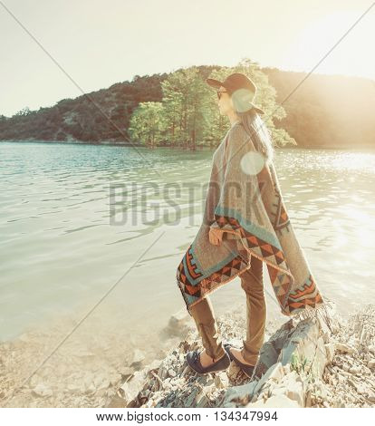Beautiful young woman wearing in hat and poncho standing on coast of lake and enjoying view of nature in summer at sunny day