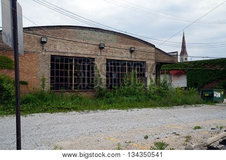 JOLIET, ILLINOIS / UNITED STATES - MAY 24, 2015: An abandoned building in downtown Joliet, with a view of the spire of the Saint Mary Carmelite Church, also abandoned.