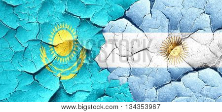 Kazakhstan flag with Argentine flag on a grunge cracked wall