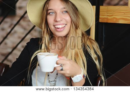 Portrait of young beautiful woman drinking coffe in a urban cafe.