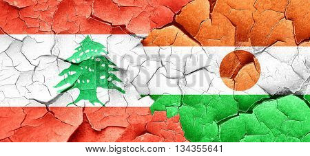 Lebanon flag with Niger flag on a grunge cracked wall