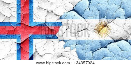 faroe islands flag with Argentine flag on a grunge cracked wall