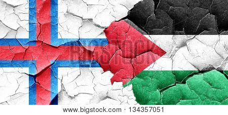 faroe islands flag with Palestine flag on a grunge cracked wall