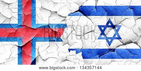 faroe islands flag with Israel flag on a grunge cracked wall
