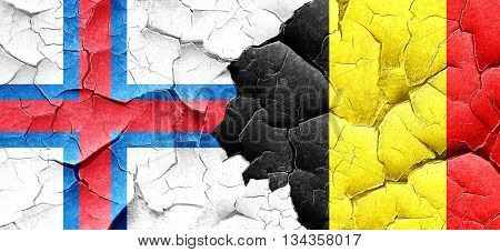 faroe islands flag with Belgium flag on a grunge cracked wall