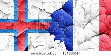 faroe islands flag with France flag on a grunge cracked wall