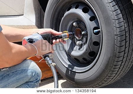 Man is changing tire with wheel wrench. Auto mechanic changing car wheel