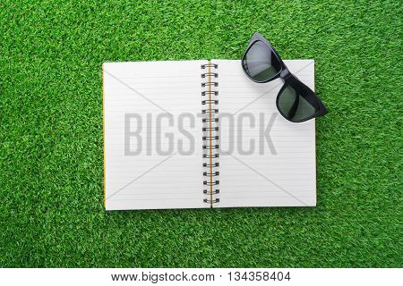 Orange notebook and sunglasses on green grass.