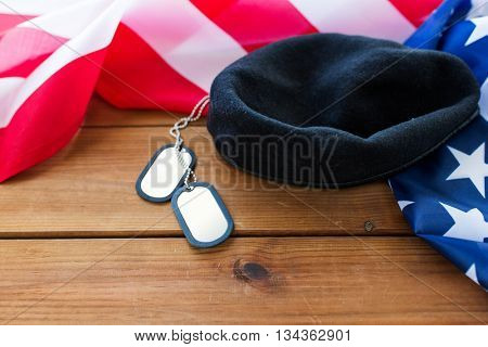 military forces, service, patriotism and nationalism concept - close up of american flag, soldiers badges and paratrooper hat on wood