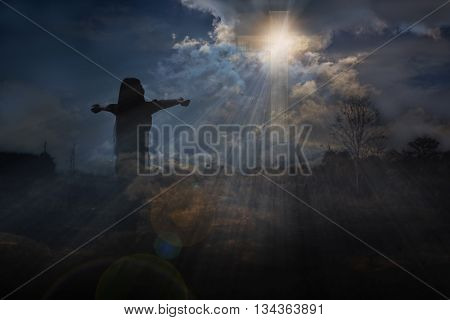 Back or rare of women with crucifix or cross form and light from dark sky God light expel darkness