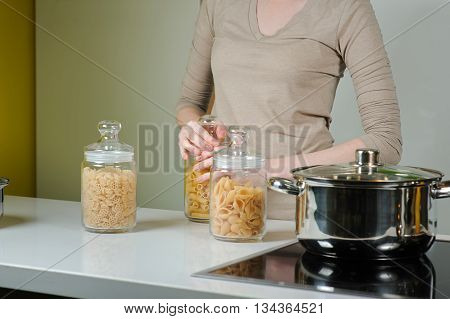 Woman cooking. Three Closed Glass jars Jar With Raw Pasta. Woman is going to cook pasta.