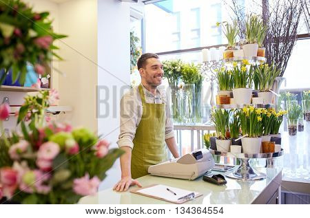 people, sale, retail, business and floristry concept - happy smiling florist man with clipboard and cashbox standing at flower shop counter
