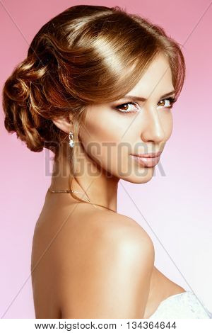 Portrait of a beautiful bride, sweet and sensual. Over pink background.