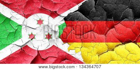 Burundi flag with Germany flag on a grunge cracked wall