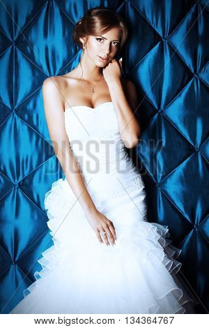 Portrait of a beautiful charming bride in a luxurious dress.