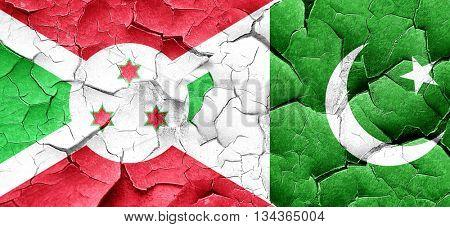 Burundi flag with Pakistan flag on a grunge cracked wall