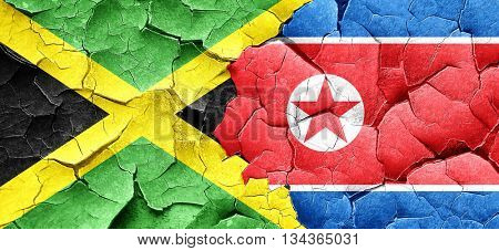 Jamaica flag with North Korea flag on a grunge cracked wall