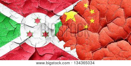 Burundi flag with China flag on a grunge cracked wall