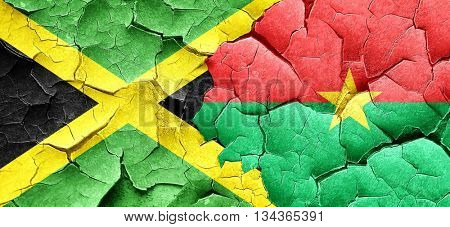 Jamaica flag with Burkina Faso flag on a grunge cracked wall